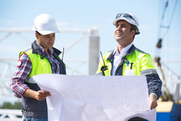 Two engineers at construction site are inspecting works on site according to design drawings.