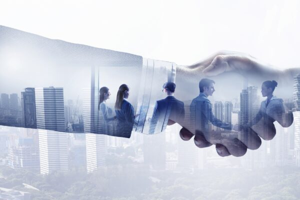 Double exposure image of business handshake and modern cityscape