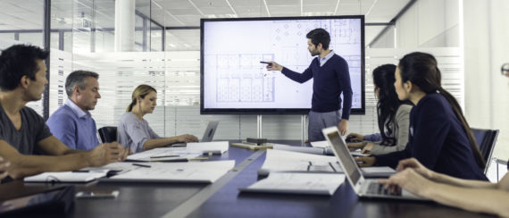 Architect standing in front of a presentation screen and pointing to it while explaining details to the audience.